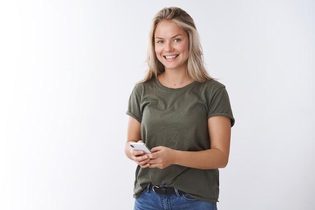 Innenaufnahme einer angenehmen, gut aussehenden, positiven frau, die herzerwärmende videos in der app empfängt und erfreut über die kamera lächelt, die das smartphone hält und nachrichten überprüft, die ein bild im sozialen netzwerk posten