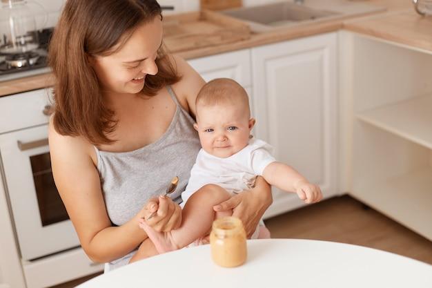 Innenaufnahme einer dunkelhaarigen frau füttert ihre kleine tochter mit obst- oder gemüsepüree, mutter schaut ihr süßes baby mit liebe an, gesunde fütterung.