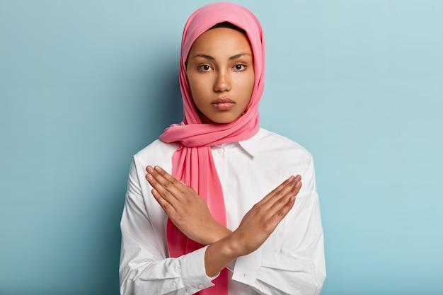 Innenaufnahme einer ernsthaften muslimischen frau macht eine handbewegung, hält die arme über der brust verschränkt, demonstriert das stoppschild, trägt ein kopftuch, folgt der religiösen kleiderordnung, isoliert über der blauen wand