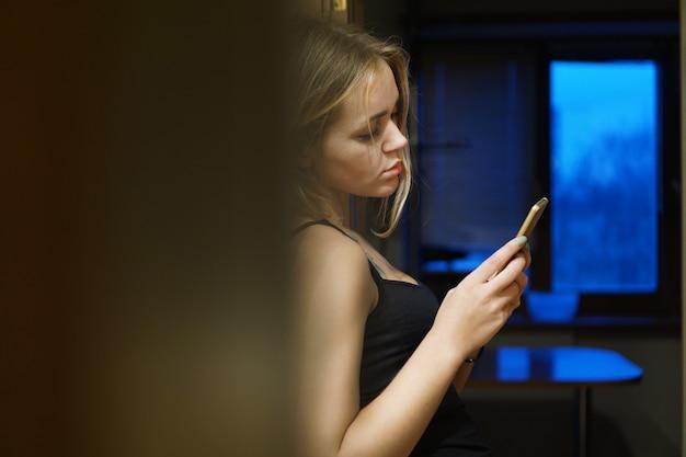 Innenaufnahme einer europäischen jungen frau hält ein modernes telefon, gekleidet in freizeitkleidung, nutzt das internet für vernetzung und kommunikation, steht in der nähe der wand