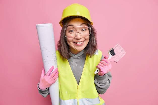 Innenaufnahme einer frohen baumeisterin, die mit hausrenovierung beschäftigt ist, hält malpinsel und bauplan trägt uniform isoliert auf rosa
