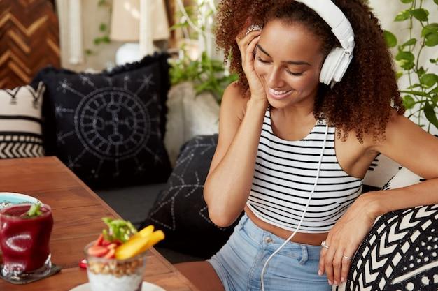 Innenaufnahme einer glücklichen frau mit dunkler haut und afro-frisur hört audiospur in kopfhörern, sieht im handy positiv aus, ruht während der pause, verwendet moderne technologien, ist mit dem internet verbunden