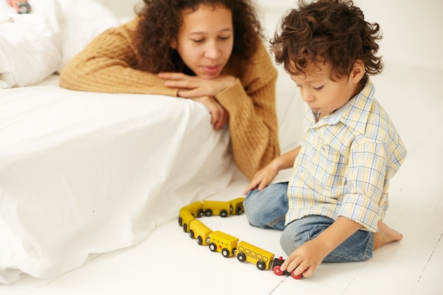 Innenaufnahme einer glücklichen jungen lateinamerikanischen frau im pullover, die ihren kleinen sohn beobachtet, der mit spielzeugbahn auf dem boden im schlafzimmer spielt, ihn nicht ablenkend. mutterschaft, kinderbetreuung, frühe entwicklung und fantasie