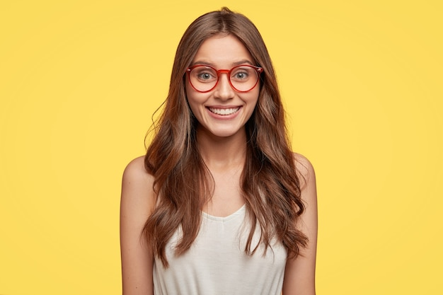 Innenaufnahme einer gut aussehenden jungen brünette mit brille, die gegen die gelbe wand aufwirft
