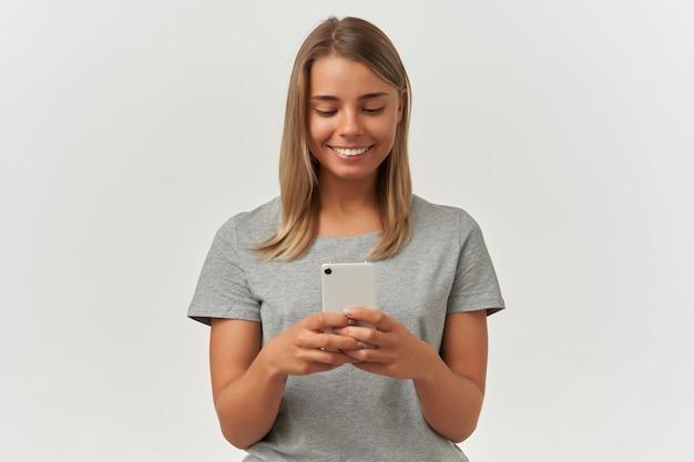 Innenaufnahme einer jungen erwachsenen frau, trägt ein graues t-shirt, schreibt mit ihrem freund eine sms, lächelt breit auf weiß