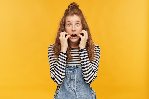 Innenaufnahme einer jungen frau mit langen roten haaren, trägt jeans-overalls und gestreiftes hemd, die vorne mit verängstigtem gesichtsausdruck die hauptrolle spielt, während sie einen horrorfilm sieht
