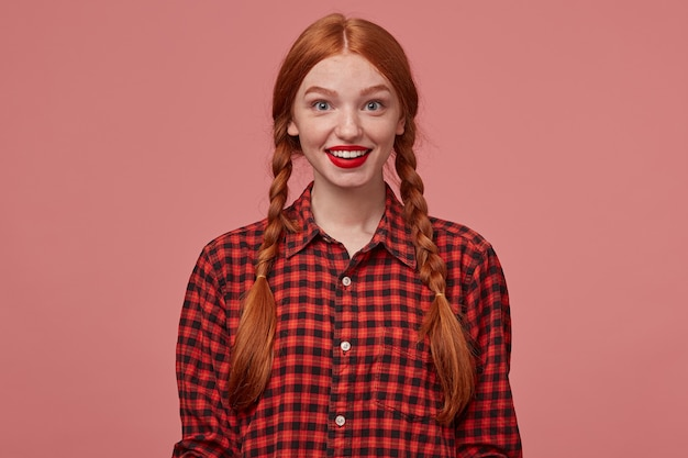 Innenaufnahme einer jungen positiven ingwerfrau, lächelt breit mit positivem gesichtsausdruck. auf rosa hintergrund isoliert