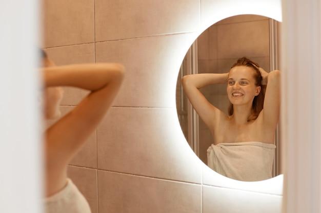Innenaufnahme einer lächelnden frau, die ihr spiegelbild mit einem charmanten, glücklichen lächeln betrachtet, mit erhobenen armen steht, die frau in ein weißes handtuch gehüllt ist.