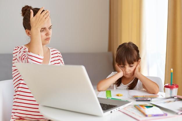 Innenaufnahme einer müden nervösen frau, die hausaufgaben mit tochter macht, die hand auf der stirn hält, weiß nicht, wie man eine aufgabe macht, schulmädchen, das mit handflächen auf den wangen vor dem laptop sitzt.