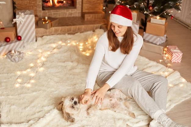 Innenaufnahme einer schönen lächelnden, glücklichen frau, die mit hund spielt, auf dem boden auf einem teppich in der nähe von weihnachtsbaum und kamin sitzt, weihnachtsmütze trägt und mit ihrem pekingese zu hause posiert.
