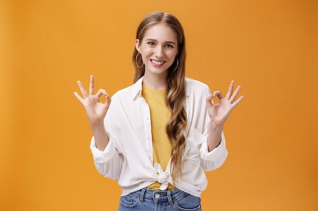 Innenaufnahme einer selbstbewussten und selbstbewussten charmanten, stilvollen frau in bluse über t-shirt und accessoires, die eine gute geste mit einem erfreuten, selbstbewussten lächeln zeigt, das gegen die orangefarbene wand in ordnung ist.