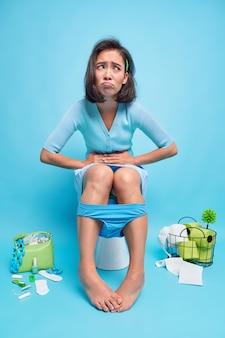 Innenaufnahme einer unzufriedenen asiatin leidet an magenschmerzen, verdauungsstörungen oder durchfall posiert in posen toilettenschüssel fühlt sich wegen bauchschmerzen unwohl, trägt höschen an den beinen