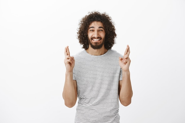 Innenaufnahme eines ängstlich glaubenden bärtigen mannes aus dem osten mit afro-frisur, der gekreuzte finger hebt und vor nervosität verzog das gesicht, um den wunsch zu erfüllen