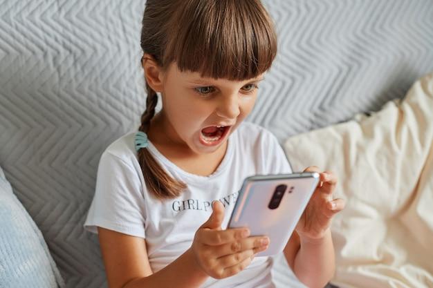 Innenaufnahme eines aggressiven weiblichen kindes, das ein weißes, lässiges t-shirt trägt und dunkles haar hat, ein smartphone in den händen hält, wütend ist, das niveau zu verlieren, vor wut schreit.
