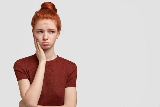 Innenaufnahme eines beleidigten teenagers spitzt die lippen, schaut mit niedergeschlagenem gesichtsausdruck beiseite