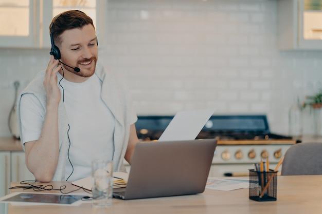 Innenaufnahme eines beschäftigten europäischen mannes hat videokurse, sieht webinar an, hört vorlesungsstudien online und trägt kopfhörer, die sich auf den laptop-bildschirm konzentrieren, der lässig gekleidet gegen die gemütliche inneneinrichtung posiert.