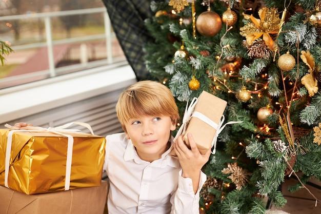 Innenaufnahme eines blonden jugendlichen jungen, der unter geschmücktem neujahrsbaum sitzt, umgeben von weihnachtsgeschenken, schüttelschachtel, versucht zu erraten, was drin ist, mit neugierigem interessiertem gesichtsausdruck