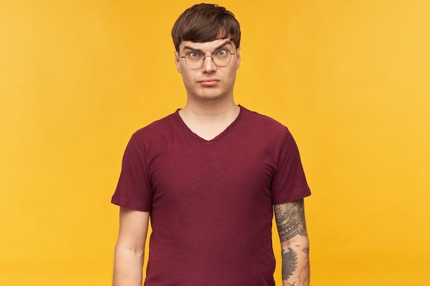Innenaufnahme eines ernsten und verwirrten jungen mannes, schaut mit gereiztem gesichtsausdruck direkt nach vorne, hält seine augenbraue hoch, trägt rotes t-shirt und runde brille