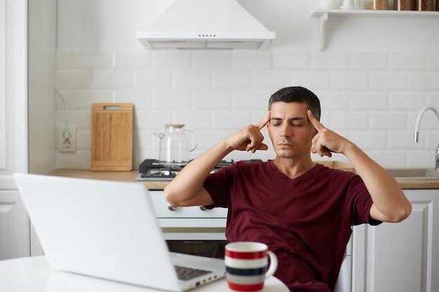 Innenaufnahme eines erschöpften mannes, der in der küche posiert, während er am tisch vor dem laptop sitzt, sich müde fühlt, die augen geschlossen hält, seine schläfen mit den fingern massiert und unter kopfschmerzen leidet.