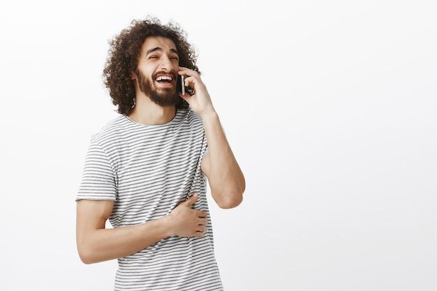 Innenaufnahme eines freudigen attraktiven freundes mit bart und afro-frisur, der beim sprechen auf dem smartphone zur seite schaut und laut lacht