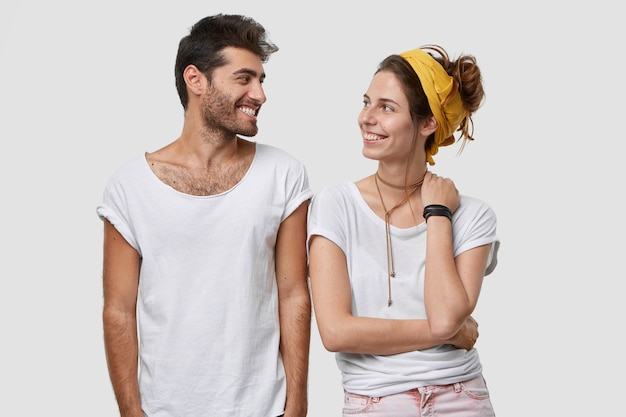 Innenaufnahme eines fröhlichen jungen bruders und einer fröhlichen schwester in freizeitkleidung, blick mit positivem ausdruck, gemeinsame freizeit genießen, über weiße wand modellieren, freundschaftliche beziehungen haben