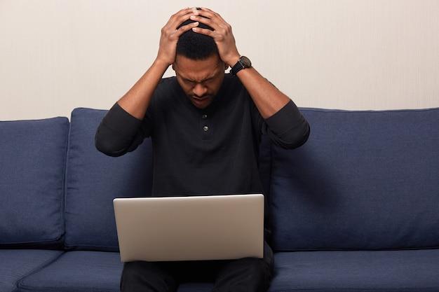 Innenaufnahme eines gestressten schwarzen jungen mannes, hält die hände auf dem kopf, versucht sich zu konzentrieren, trägt einen schwarzen freizeitpullover, arbeitet am laptop, nutzt wireless internrt und sitzt auf einem bequemen sofa.