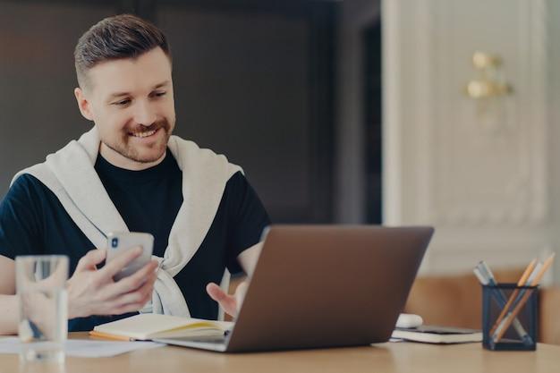 Innenaufnahme eines glücklichen männlichen freiberuflers verwendet moderne gadgets, sucht informationen über laptop-computer, moderne smartphone-posen auf dem desktop gegen gemütliche inneninstallationenneue anwendung verwendet das internet