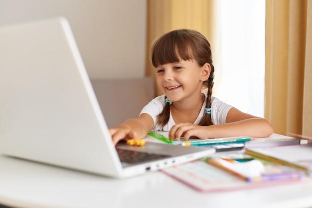 Innenaufnahme eines glücklichen, positiven dunkelhaarigen schulkindes, das zu hause posiert, einen tragbaren computer mit charmantem lächeln betrachtet, fernunterricht, online-unterricht hat.