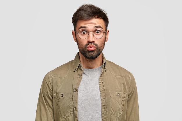 Innenaufnahme eines gutaussehenden verwirrten mannes hält die lippen rund, öffnet die augen weit und ist überrascht, eine großartige idee von einem freund zu hören
