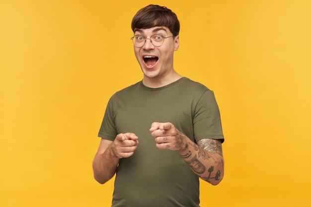 Innenaufnahme eines jungen männlichen studenten, hält den mund weit geöffnet, zeigt mit beiden zeigefingern vorne an