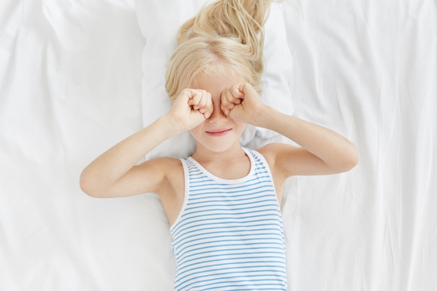 Innenaufnahme eines kleinen mädchens, das sich am morgen nach dem aufwachen die augen reibt, auf einer weißen bettdecke liegt und mehr schlafen möchte. schläfriges kind, das auf dem bett liegt und müden ausdruck hat, während es schlafen möchte