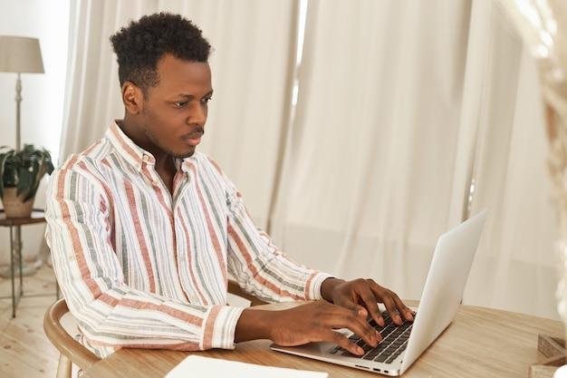 Innenaufnahme eines konzentrierten afrikanischen studenten, der online über laptop über drahtlose internetverbindung lernt, am schreibtisch sitzt, hausaufgaben macht oder sich auf die prüfung vorbereitet.