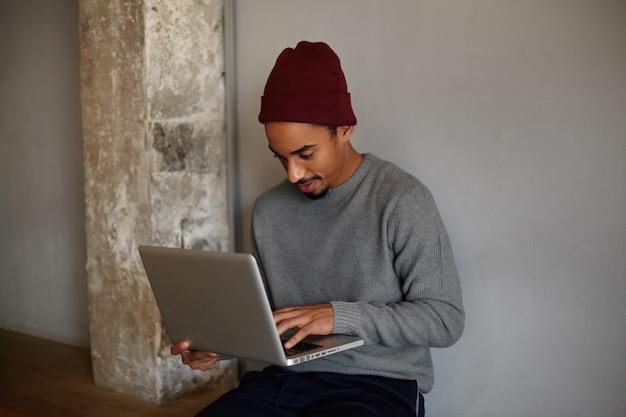 Innenaufnahme eines konzentrierten, schönen, dunkelhäutigen mannes mit bart, der einen laptop hält und mit einem nachdenklichen gesicht auf den bildschirm schaut und über einer weißen wand in freizeitkleidung sitzt