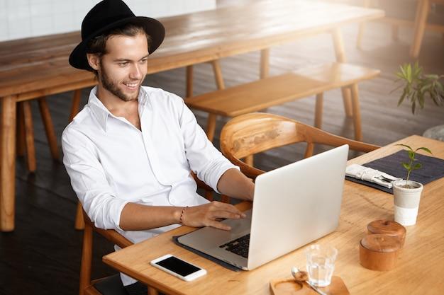 Innenaufnahme eines männlichen bloggers, der auf der tastatur eines laptops tippt, kostenloses wi-fi im modernen café verwendet, während er an seinem neuen beitrag in den sozialen netzwerken arbeitet und bildschirm mit glücklichem und inspiriertem gesichtsausdruck betrachtet