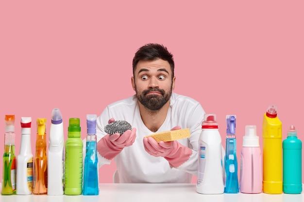 Innenaufnahme eines überraschten bärtigen mannes sieht mit herausgesprungenen augen aus, trägt freizeitkleidung, verwendet verschiedene reinigungsmittel