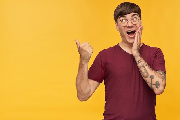 Innenaufnahme eines überraschten positiven jungen mannes, mit einem daumen auf den kopierraum zeigen, mit überraschtem gesichtsausdruck