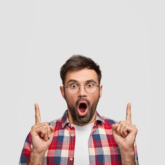 Innenaufnahme eines verwirrten bärtigen mannes zeigt nach oben und ist erstaunt, während er gegen die weiße wand posiert.