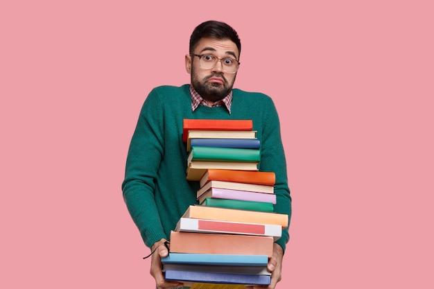 Innenaufnahme eines verwirrten unrasierten mannes trägt eine brille, hält viele handbücher, fühlt zweifel