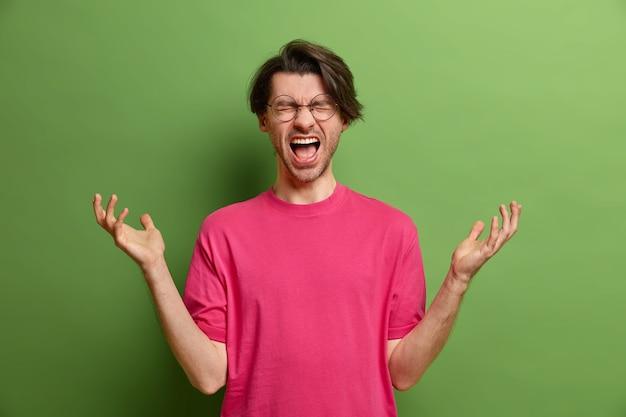 Innenaufnahme eines verzweifelten wütenden mannes ruft laut aus und hebt die hände mit frustriertem gesichtsausdruck hat fehler oder probleme im leben