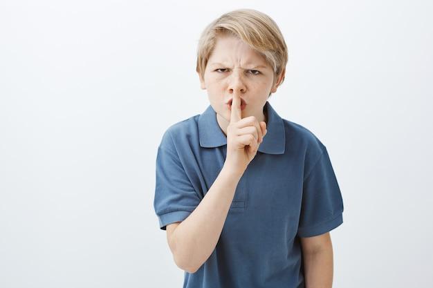Innenaufnahme eines wütenden, genervten, blonden bruders in einem lässigen t-shirt, der die stirn runzelt und shh sagt, während er mit dem zeigefinger über dem mund eine shush-geste macht und verlangt, ruhig zu bleiben