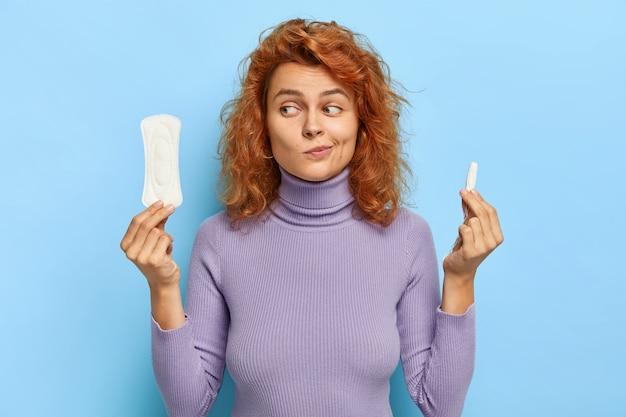 Innenaufnahme eines zweifelhaften weiblichen modells zögert zwischen zwei hygieneprodukten