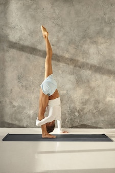 Innenaufnahme in voller länge eines nicht erkennbaren sportlichen muskulösen mannes in sportbekleidung, der yoga praktiziert, eine stehende split-pose macht oder urdhva prasarita eka padasana, kniesehnen, waden und oberschenkel streckt