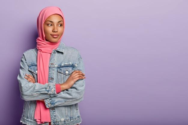 Innenaufnahme nachdenklich schöne arabische frau steht drinnen mit gekreuzten händen, fokussiert weg, denkt über zukünftige pläne nach, trägt hijab und jeansmantel, isoliert über lila wand.
