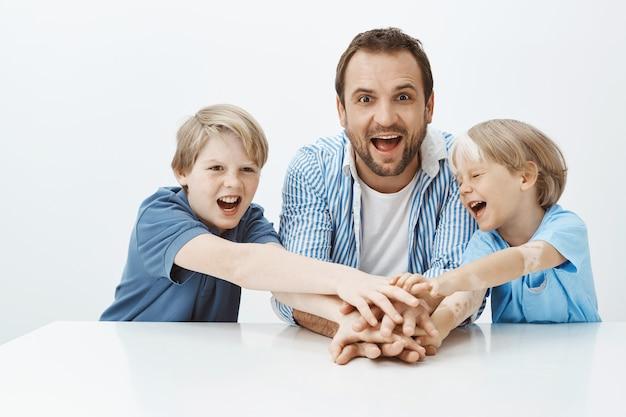 Innenaufnahme von freudigen attraktiven jungen und vater, die am tisch sitzen, hände halten, lachen und vor glück schreien. papa tut sich mit söhnen zusammen, um mama ein geschenk zu machen