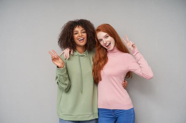 Innenaufnahme von fröhlichen schönen jungen damen, die hände mit siegesgeste heben und glücklich mit breitem lächeln schauen, während sie über grauer wand stehen