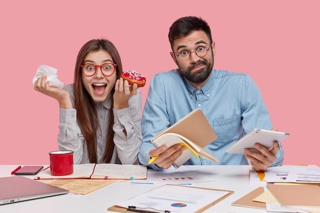 Innenaufnahme von mitarbeitern von frau und mann essen leckeren donut, schreiben notizen in notizbuch, verwenden moderne technologien