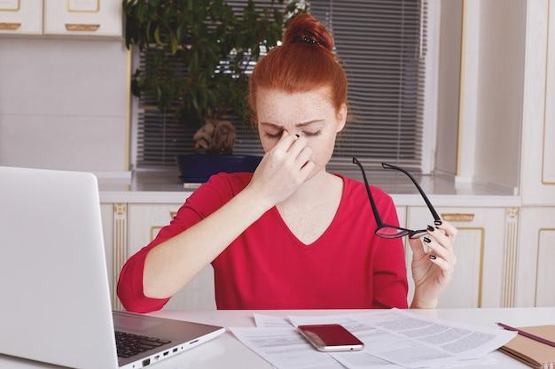 Innenaufnahme von müdigkeit überarbeitete unternehmerin nimmt brille ab