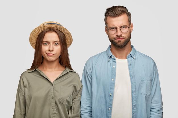 Innenaufnahme von mürrischen unzufriedenen familienpaar-geldbeutellippen mit unangenehmem blick