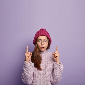 Innenaufnahme von überraschten verängstigten jungen kaukasischen weiblichen punkten oben mit beiden zeigefingern, trägt transparente brille, winterkleidung, isoliert gegen lila wand, freier raum nach oben