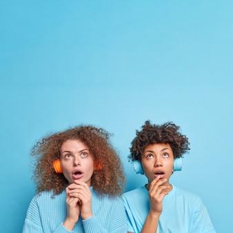 Innenaufnahme von zwei gemischten jungen frauen, die sich mit überraschten, verwunderten ausdrücken über dem kopf konzentrierten, musik in drahtlosen kopfhörern hören und etwas erstaunliches isoliert über der blauen wand bemerken